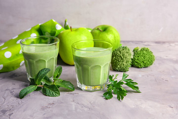 Glasses of fresh juice and apples on grunge background