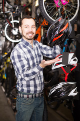 Man shows helmets for cycling