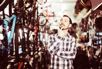 Man selects bicycle in sporting goods store