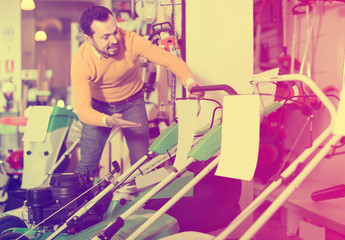 concentrated guy deciding on best lawnmower in garden equipment shop