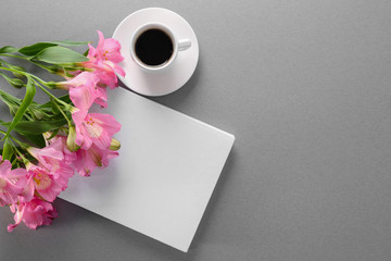 Book with blank white cover, cup of coffee and beautiful flowers on gray background