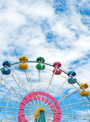 Colorful ferris wheel over blue sky.
