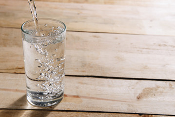 Pour drinking water into a glass of water.