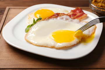 Eating delicious over easy eggs with bacon on kitchen table