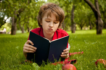 sad bored surprised teen boy reading a book in the green summer apple trees park