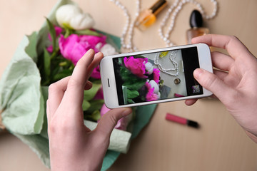 Female hands taking picture of beautiful peony flowers and accessories, closeup