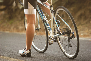 A close up to the legs of a female cyclist sitting on her road bike during sunset_