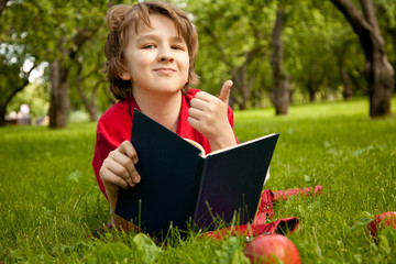 teen boy reading a book in the green summer apple trees park