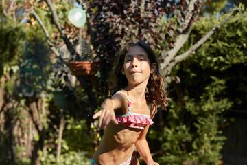 Girl in bikini throwing water balloon.