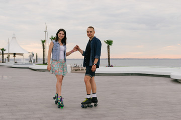 Beautiful sweet couple riding on roller skates quads holding hands near the sea