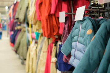 Variety of modern winter jackets on hangers in outdoor sports store