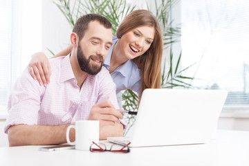 Cheerful young couple working on laptop.