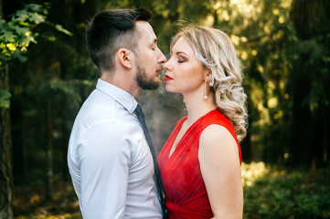 Closeup of couple of lovers kissing with smoke outdoor.  Businessman and young blonde girl with red lips, curly hair and red dress with decolette. Smokers in forest in summer sunny day. Sensual moment