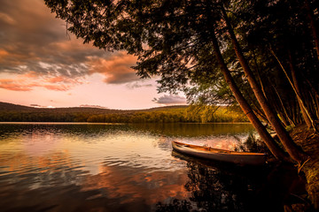 Canoe on the lake at sunset. Warm sunset colors spill over Mongaup Pond, the largest lake in the Catskills. One of the most popular summer vacation and camping destination in New York