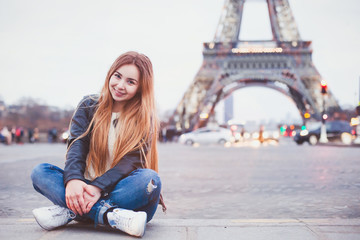 smiling happy beautiful woman tourist in Paris looking at camera, portrait of caucasian girl near Eiffel Tower