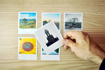 Hand choosing a photo among six options over a wood tabletop