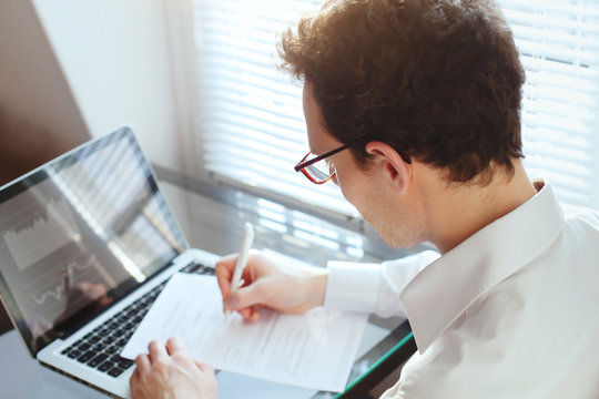 businessman manager working with financial data and papers in the office, writing report