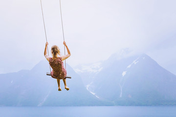 happiness concept, happy girl child on the swing on beautiful mountain landscape background