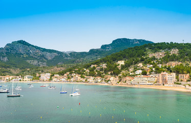 Puerto de Soller, Port of Mallorca island in balearic islands, Spain. Beautiful  beach and bay with boats in clear blue water of summer day.