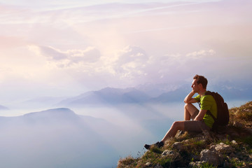 man sitting on top of mountain, achievement or opportunity concept, hiker looking forward on beautiful panoramic landscape