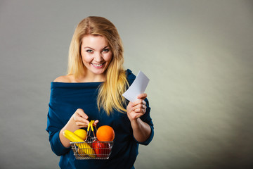 Happy woman holding shopping basket with fruits