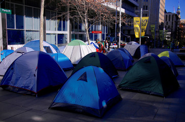 A group of homeless people sit near their tents they have erected outside the main entrance to the Reserve Bank of Australia building located in central Sydney, Australia