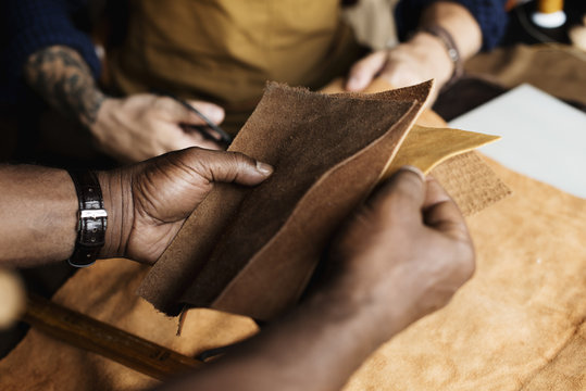 Closeup of craftsman holding leather handicraft