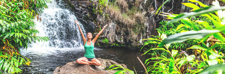 Yoga nature waterfall wellness retreat woman banner meditating. Meditation happy girl with open arms in serenity enjoying lush forest outdoors, mindfulness concept. Banner panorama crop.