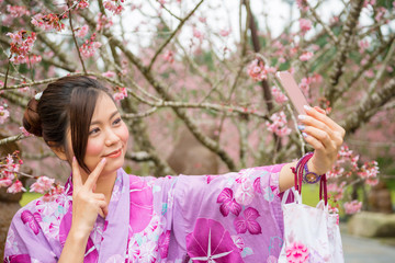 Asian girl taking selfie photo at sakura park