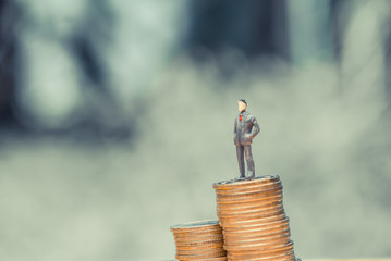Miniature people, small figures businessmen stand on top of coins. Business concept. shallow focus in soft tone.