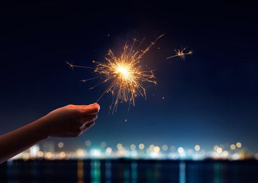 Female hand holding a burning sparkler
