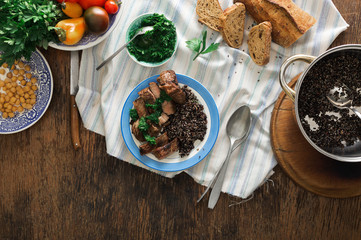 Plate with steak grilled and black quinoa on wooden table