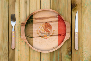 Concept of Mexican cuisine. Wooden plate with a Mexican flag, fork and knife on a wooden background