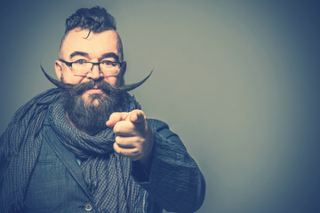 Adult bearded man with a mohawk hairstyle and with a very long mustache showing forefinger forward. Toned