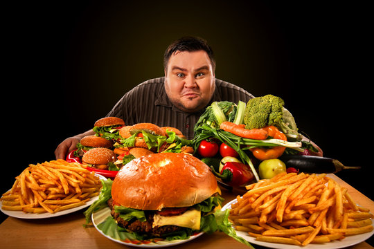 Diet fat man who makes choice between healthy and unhealthy food . Overweight male with hamburgers, french fries and vegetables trays trying to lose weight first time number one.