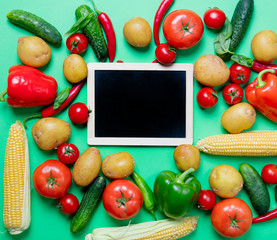 tomatoes and potatoes with blackboard and vegetables