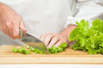 Chef's hands with knife cutting a green salad leaves on the wooden board. Preparation for cooking. Healthy eating and lifestyle.