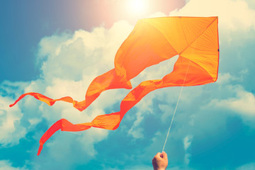Orange kite in hand in sunny blue sky with clouds