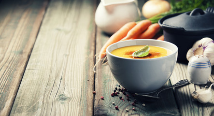 Vegetable cream soup in bowl over old wooden background