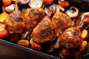Roasted chicken legs with vegetables on wooden background