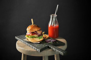 Composition with delicious homemade burger, tomato juice and vegetables on wooden table