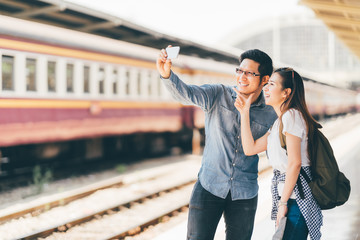 Young Asian couple traveler taking selfie together using smartphone waiting for trip at train station platform in Asia. Backpack travel, Love relationship, holiday vacation or modern lifestyle concept