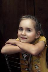 Портрет маленькой девочки в комнате на стуле.