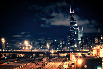 Wall Mural - Chicago skyline cityscape at night featuring a train yard and urban bridge with a dramatic cloudy sky.