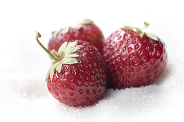 Sweet strawberry isolated over white sugar background.