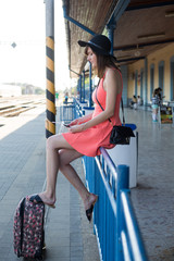 Beautiful young caucasian woman sitting on a railing at the train station, resting her feet on her suitcase.