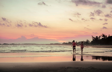A pair of lovers running along the beach at sunset