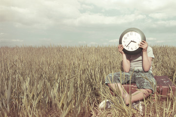 Boy on a trip hides his face with a clock in a desert landscape