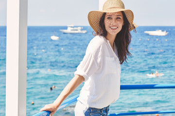 Young beautiful woman in a straw hat resting by the sea