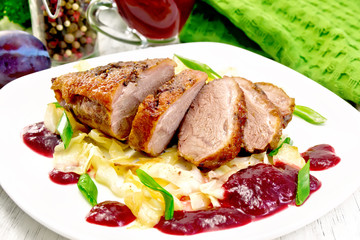 Wall Mural - Duck breast with plum sauce and cabbage in plate on board